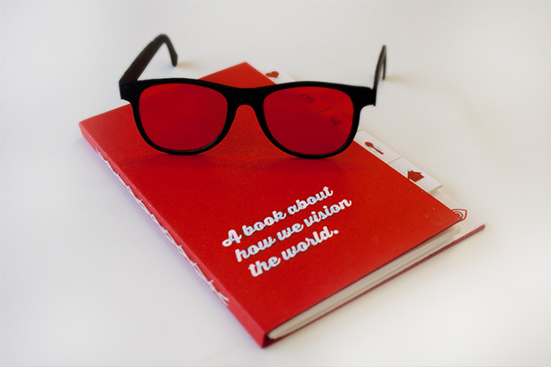 Mandi Halonen student project - a pair of black rimmed spectacles on top of a red book with cover title 'A book about how we vision the world'