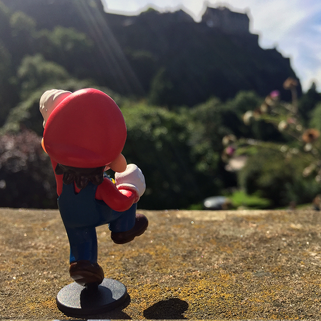 Mario throwing a fist into the air with Edinburgh Castle in the background.