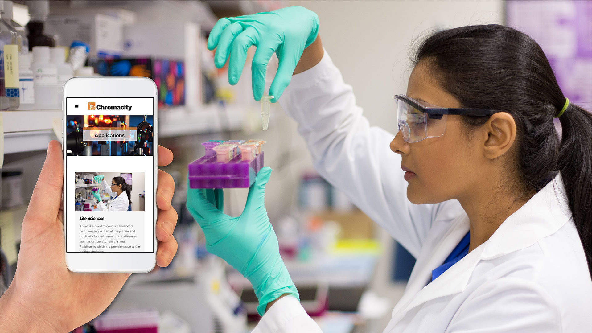 iPhone displaying Chromacity website against backdrop of scientist with test tubes