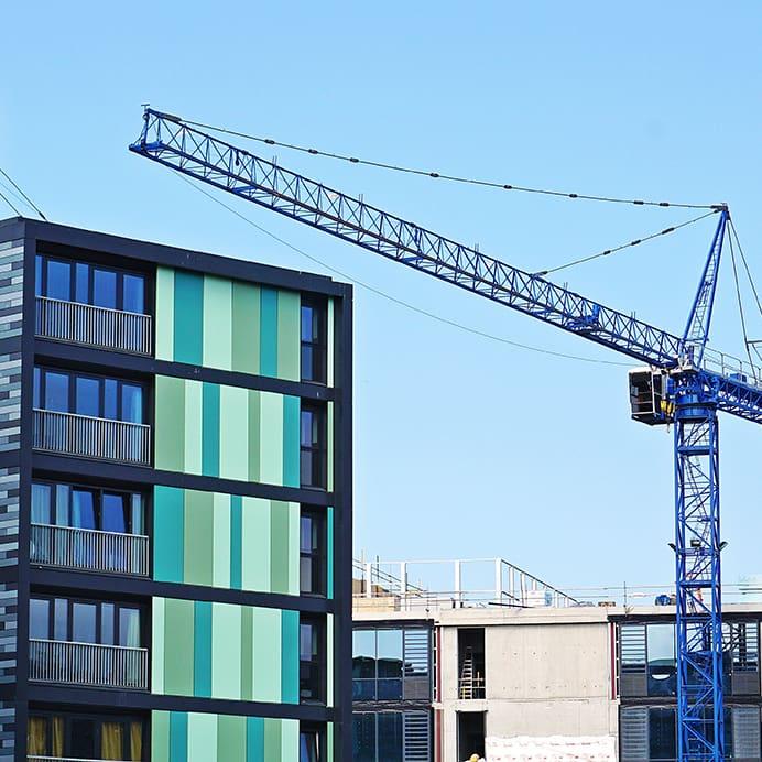 A crane against a blue sky, beside high-rise buildings