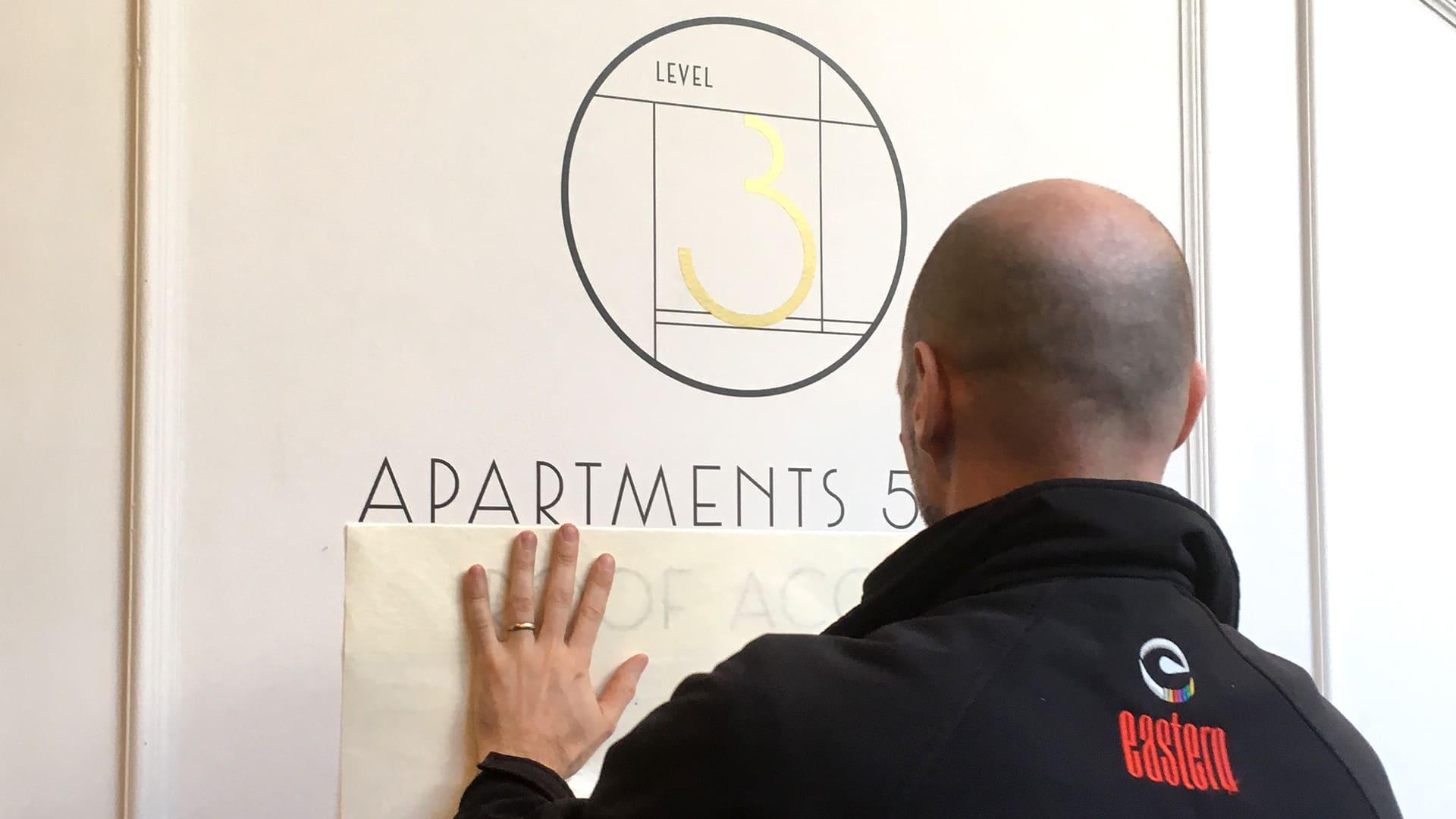 Man installing signage at Kingsford Residence